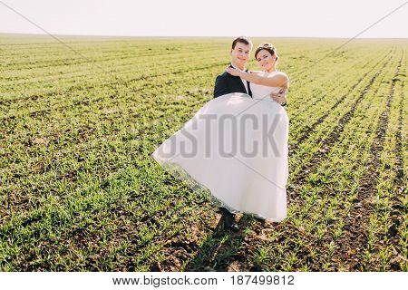 The full-length view of the groom carrying the bride at the background of the field