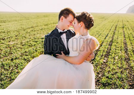 Romantic close-up portrait of the groom carrying the bride at the background of the green field