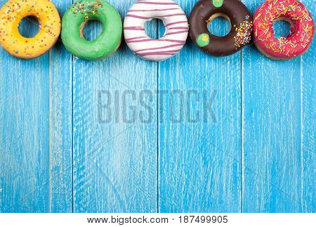 glazed donuts on a blue wooden background with copy space for your text. Top view.