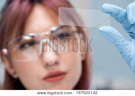 Close-up View Of Concentrated Young Scientist In Eyeglasses Holding Glass Microscope Slide In Chemic