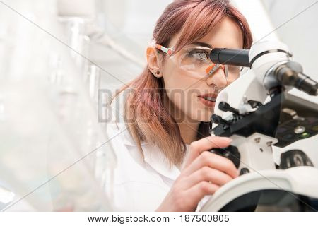 Portrait Of Scientist In Lab Coat Looking Through Microscope In Laboratory