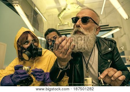 grey hair man with beard taking drugs with women in personal protective equipment drugs concept
