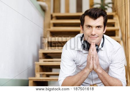 Portrait of young man sitting at the stairs in office