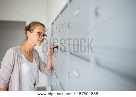 Pretty, young woman checking her mailbox for new letters