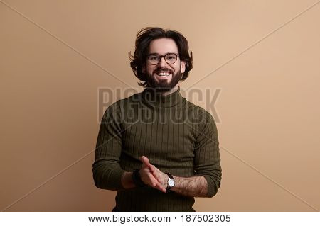 Horizontal studio shot of smiling bearded man in glasses looking at camera.