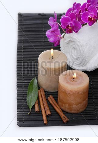 Spa setting with branch orchid, towel, cinnamon, candle,leaf.mat