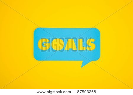 Cut-out goals word in blue colored talk bubble isolated on yellow.
