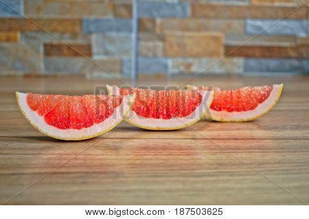 Closeup of grapefruit wedges on a wooden table