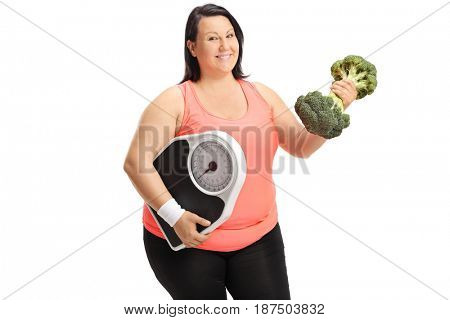 Overweight woman with a weight scale and a broccoli dumbbell isolated on white background