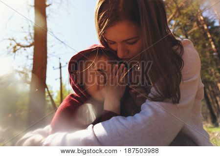 Mother and little child having fun together. Young woman hugging her son, happy smiling mom with kid playing outdoors. Family concept.