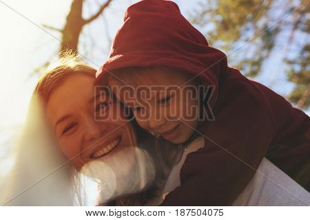 Portrait of smiling mother and son playing together in park. Little son hugging his young mom, having fun together. Happy family concept.