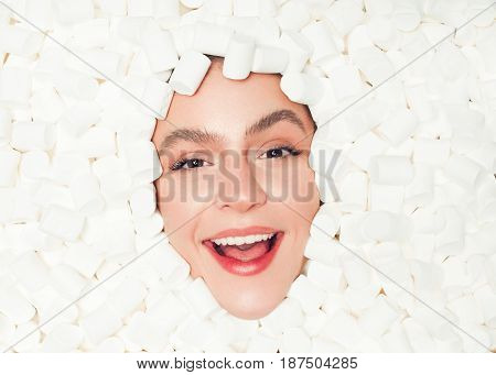 Horizontal close-up shot of excited woman looking at camera from a pile of marshmallows.