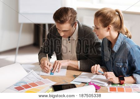 Professional designer. Professional nice handsome man holding a ruler and drawing while sitting at the table with his colleague