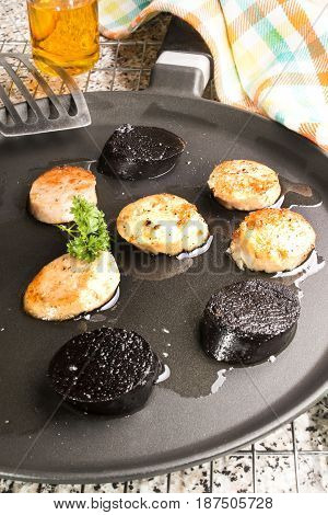 grilled irish white and black pudding with spatula on a pan