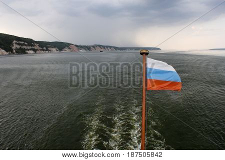 Russian flag on the stern of the river boat, river landscape, photographed from the ship