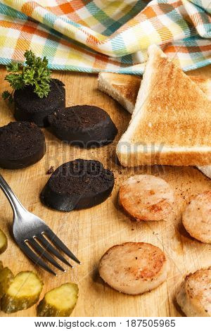 black and white pudding with toast bread and gherkin on a wooden board