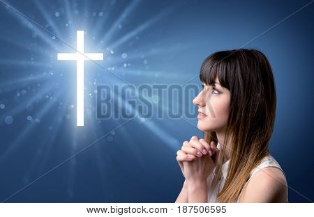 Young woman praying on a blue background with a sparkling cross above her
