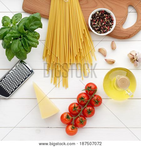 Dry Pasta Bucatini Or Spaghetti With Basil, Oil, Cheese, Tomatoes On White Wooden Background.