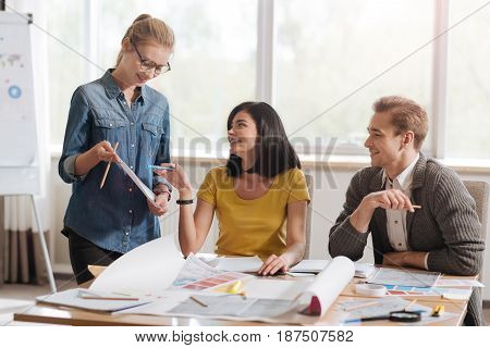This is it. Positive delighted beautiful woman holding a pen ant pointing at the sketch while looking at her colleague