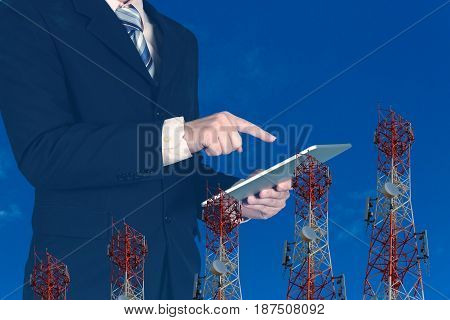 Double Exposure Of Businessman Using Tablet On Blue Sky And Telecommunication Tower