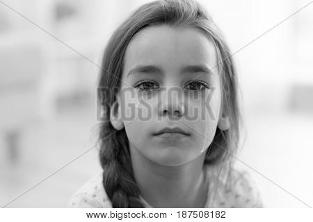 Sad little girl on blurred background