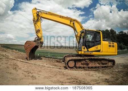 Yellow excavator standing on mud ground ready for working