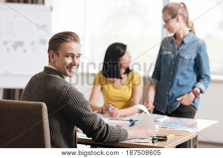 Interesting job. Handsome cheerful designer sitting at the table and looking at you while working with his colleagues