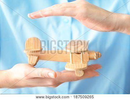 Female hands and wooden toy airplane. Travel insurance concept