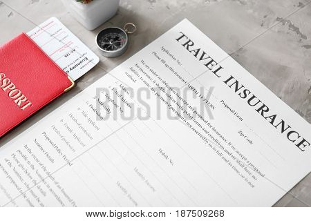 Passport with ticket and blank travel insurance form on grey background