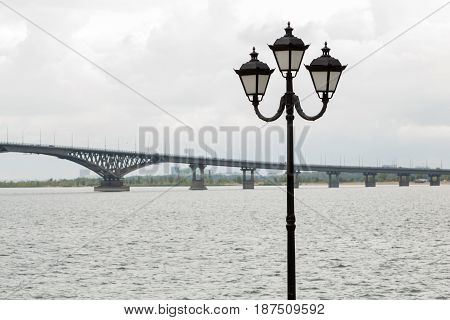 Bridge across the Volga river between the cities of Saratov and Engels, promenade, street light, cloud, September
