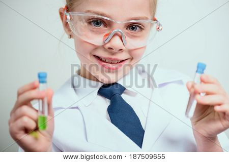 Schoolgirl In Goggles Holding Reagents In Flasks Isolated On Grey, Science Student Concept
