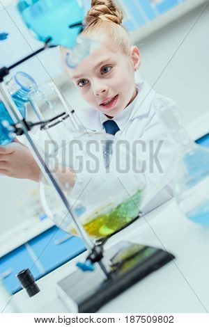 Schoolgirl In White Coat Making Experiment With Reagents In Chemical Lab, Science Student Concept