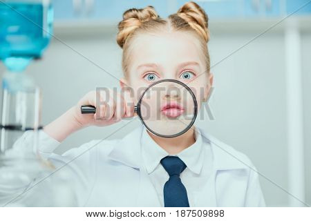 Little scientist in white coat holding magnifier in chemical lab science school concept