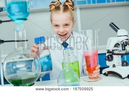 Schoolgirl In White Coat Making Experiment With Reagents In Science Laboratory