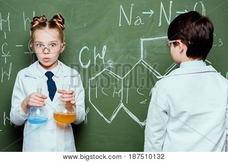 Boy And Girl In White Coats Standing With Reagents In Flasks And Drawing Chemical Formulas In Scienc