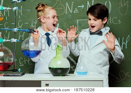 Little Kids In White Coats With Chalkboard Behind In Laboratory, Scientists Kids Team Concept