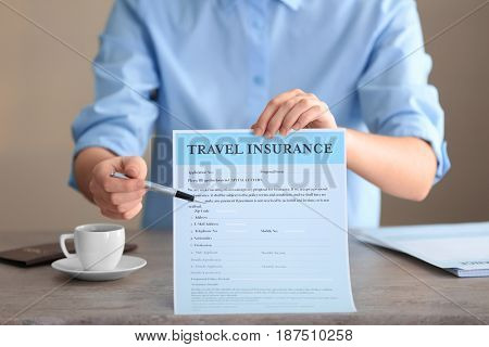 Woman sitting at table and pointing with pen on blank travel insurance form