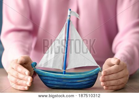 Female hands and wooden toy boat on table. Travel insurance concept