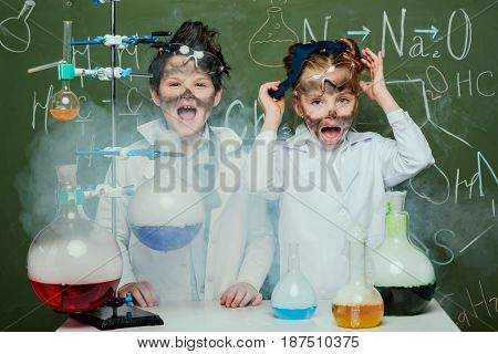 Little Kids In White Coats With Chalkboard Behind In Science Laboratory