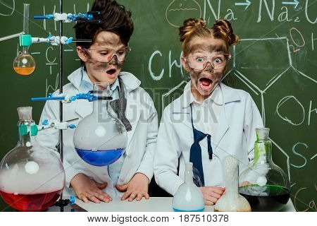 Little Kids In White Coats With Chalkboard Behind In Science Laboratory, Scientists Kids Team Concep