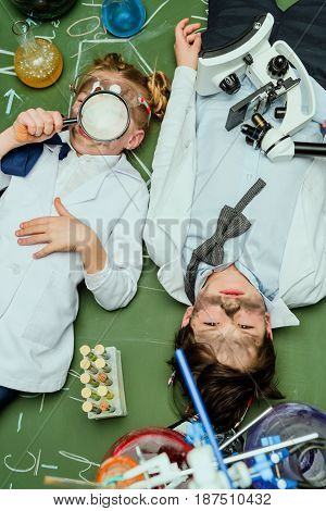 Elevated View Of Kids In Lab Coats Lying On Chalkboard After Experiment, Scientists Kids Team Concep