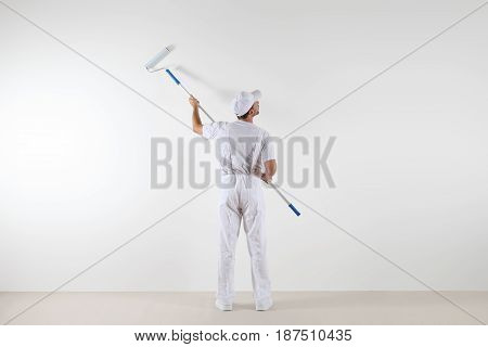 Rear view of painter man looking at blank wall with paint roller stick isolated on white room