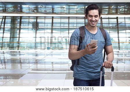 Handsome Asian Man Traveler With Suitcase Holding Smartphone