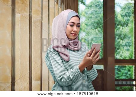 Pretty Asian Muslim Woman With Veil Holding Mobile Phone