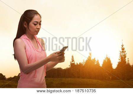 Young Asian Athlete Woman With Smartphone After Exercising