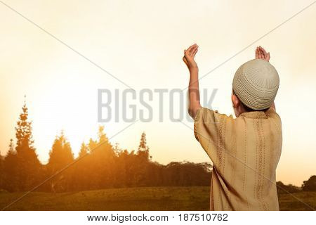 Back View Of Asian Muslim Kid With Cap Praying To God