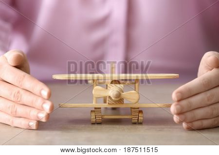 Female hands and wooden toy airplane on table. Travel insurance concept