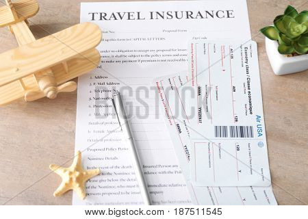 Tickets and pen on travel insurance form