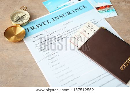 Passport with ticket and compass on travel insurance form