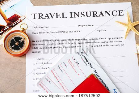 Tickets and compass on travel insurance form, closeup